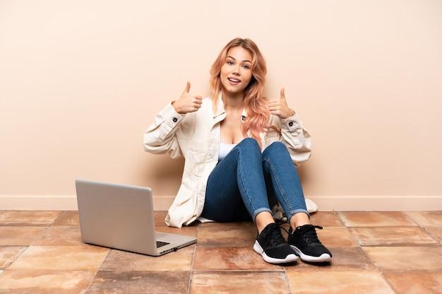 Mulher adolescente com um laptop sentada no chão dentro de casa fazendo um gesto de polegar para cima