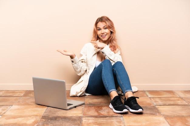 Mulher adolescente com um laptop sentada no chão em um ambiente fechado, segurando o imaginário de copyspace na palma da mão para inserir um anúncio