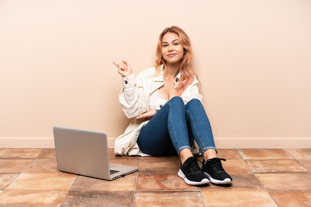 Mulher adolescente com um laptop sentada no chão em uma área interna apontando o dedo para o lado