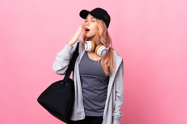 Mulher adolescente com uma bolsa esportiva sobre uma parede isolada, bocejando e cobrindo a boca aberta com a mão