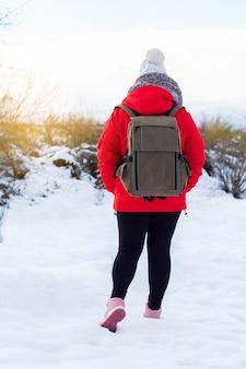 Mulher adolescente de jaqueta vermelha, chapéu e mochila, olhando para a paisagem nevada das florestas e montanhas em uma excursão. sensação de liberdade e tranquilidade. vertical.