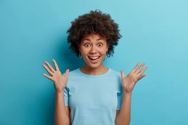 Mulher adolescente de pele escura, feliz e animada levanta as palmas das mãos e sorri alegremente surpresa