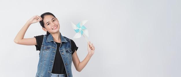 Mulher adolescente e brinquedos de moinho de vento de papel retrato adolescente com roda de vento de papel de cor azul vara de madeira