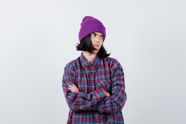 Mulher adolescente em pé com os braços cruzados, mostrando a língua
