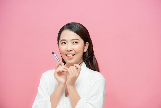 Mulher adolescente encantadora aplicando rímel / conjunto de fotos de uma garota atraente em fundo rosa