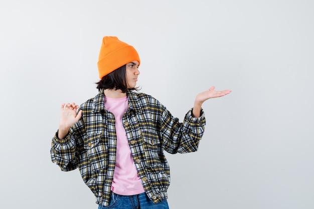 Mulher adolescente fingindo mostrar algo em uma camiseta e parecendo focada