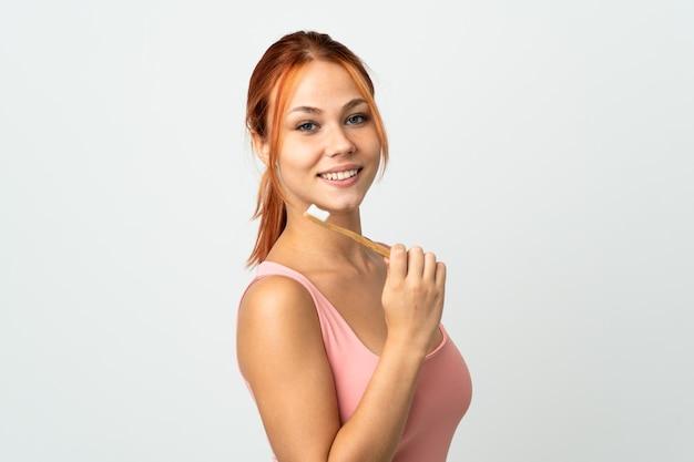 Mulher adolescente isolada com uma escova de dentes e uma expressão feliz