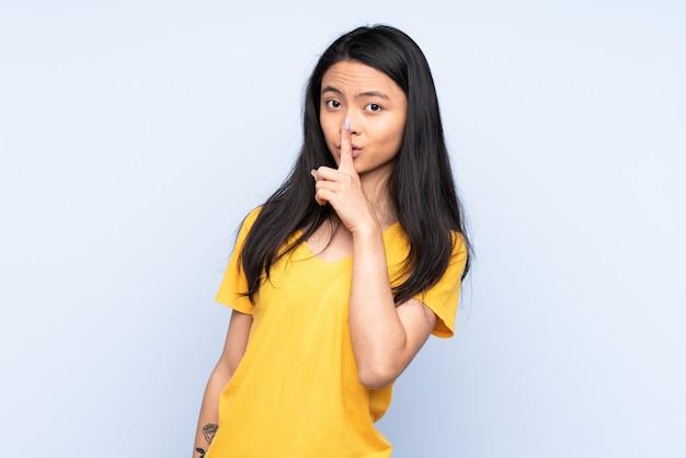 Mulher adolescente isolada em azul, mostrando um sinal de gesto de silêncio colocando o dedo na boca