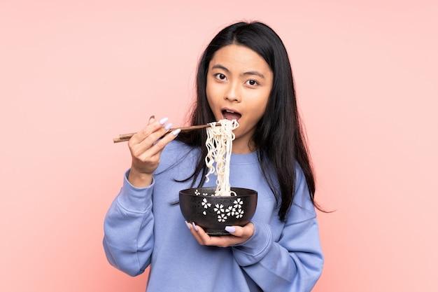 Mulher adolescente isolada em bege, segurando uma tigela de macarrão com pauzinhos e comê-lo