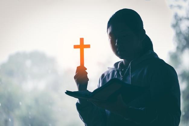 Mulher adolescente, mão, com, cruz, e, bíblia, orando mãos, dobrado, em, oração, ligado, um, bíblia sagrada