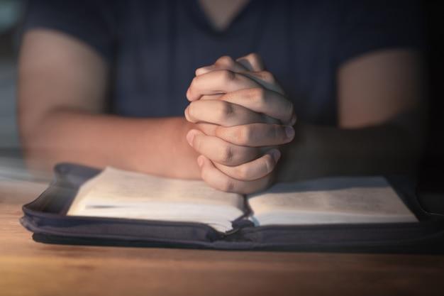 Mulher adolescente, mão, com, cruz, e, bíblia, orando, mãos, dobrado, em, oração