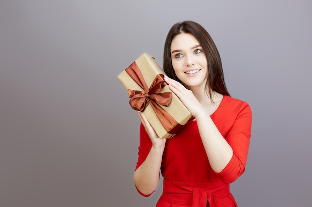 Mulher adolescente morena com um vestido vermelho brilhante recebe um presente para o feriado.
