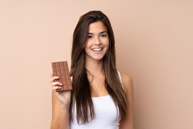 Mulher adolescente parede isolada tomando uma tablete de chocolate e feliz