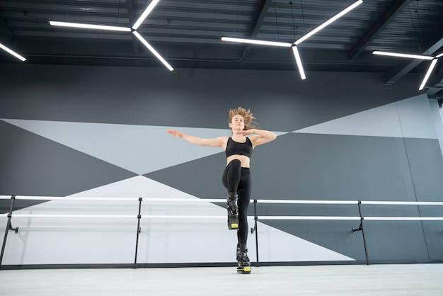 Mulher adolescente praticando saltos de kangoo dentro de casa