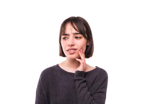 Mulher adolescente pressionando a bochecha machucada com uma expressão dolorida, como se estivesse tendo uma terrível dor de dente.