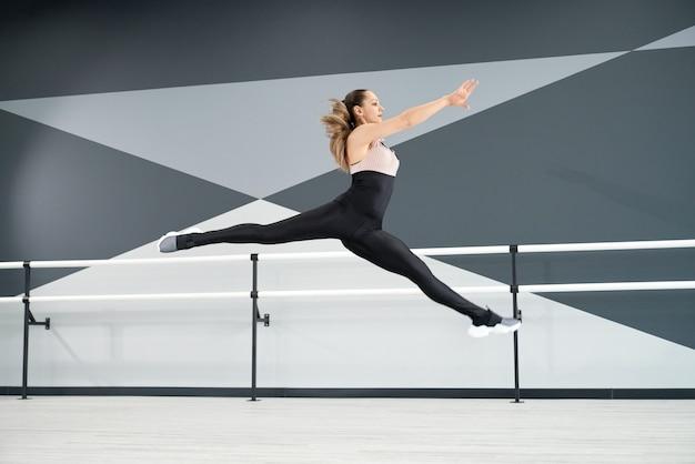 Mulher adolescente pulando praticando rachaduras no ar