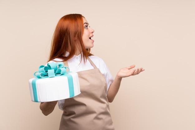 Mulher adolescente ruiva com um bolo grande com expressão facial de surpresa
