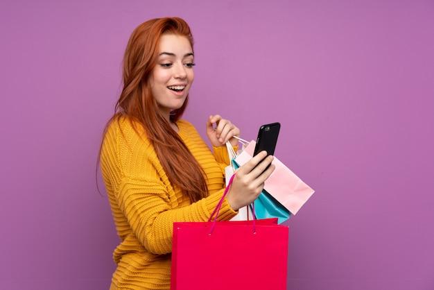 Mulher adolescente ruiva sobre parede roxa isolada segurando sacolas de compras e escrever uma mensagem com o celular para um amigo