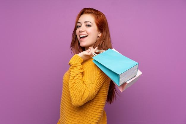 Mulher adolescente ruiva sobre parede roxa isolada segurando sacolas de compras e sorrindo