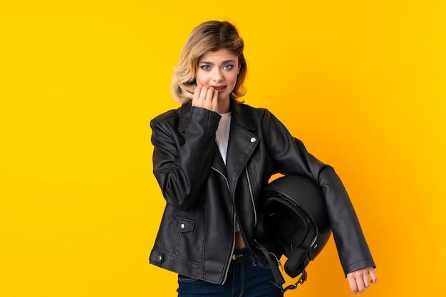 Mulher adolescente segurando um capacete de motocicleta isolado em amarelo, nervosa e assustada