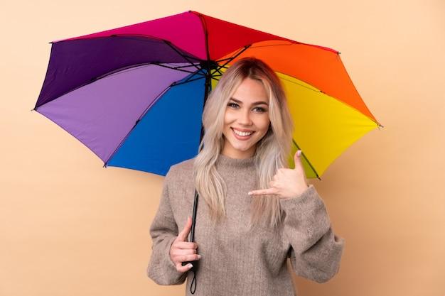 Mulher adolescente segurando um guarda-chuva sobre parede isolada, fazendo gesto de telefone