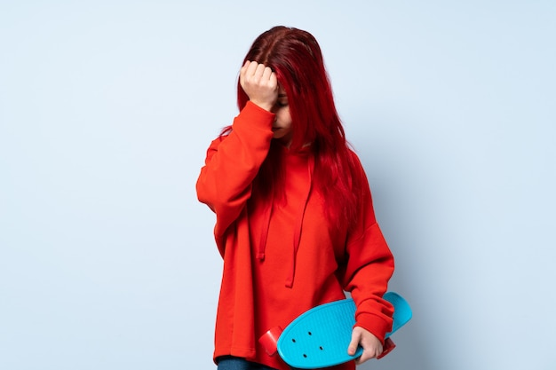 Mulher adolescente skatista isolada na parede branca com dor de cabeça