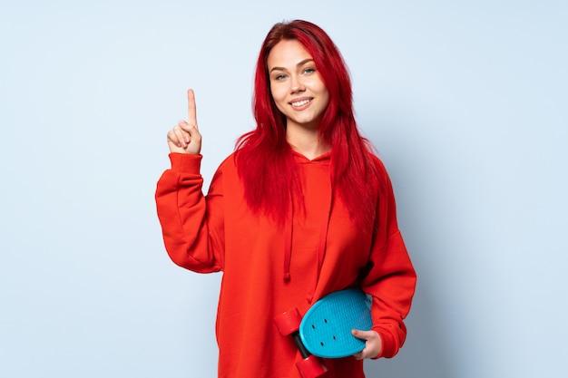 Mulher adolescente skatista isolada na parede branca, mostrando e levantando um dedo em sinal dos melhores