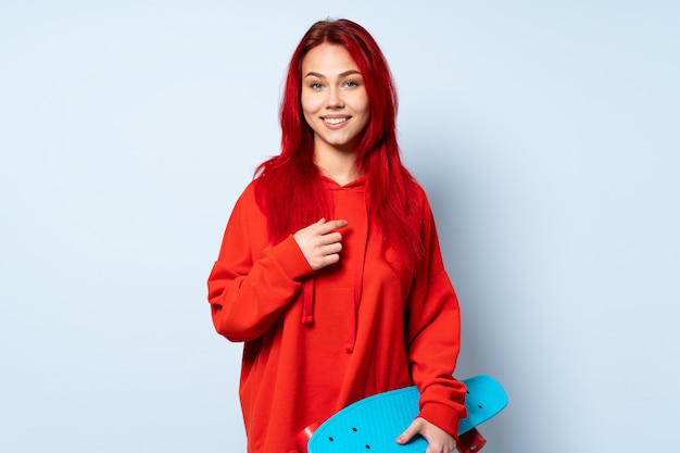 Mulher adolescente skatista isolada na parede branca rindo