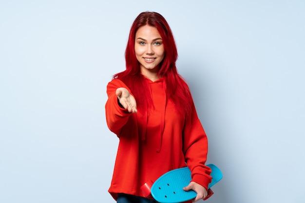 Mulher adolescente skatista isolada na parede branca segurando copyspace imaginário na palma da mão para inserir um anúncio
