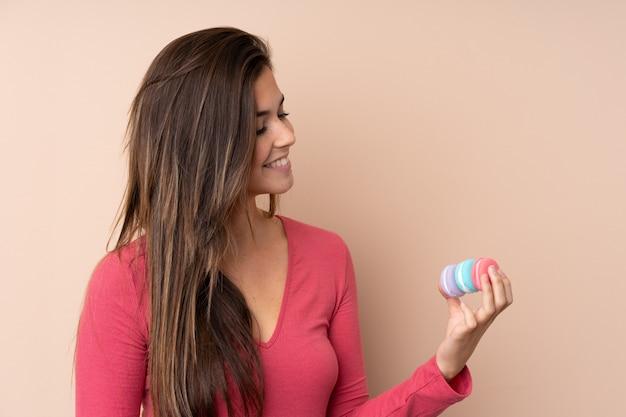 Mulher adolescente sobre parede isolada segurando feliz macarons franceses coloridos e