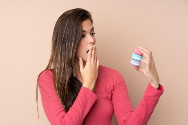 Mulher adolescente sobre parede isolada segurando macarons franceses coloridos e com expressão de surpresa