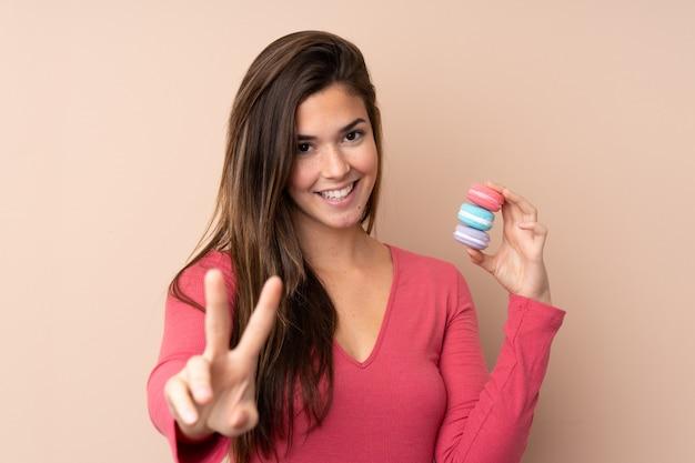 Mulher adolescente sobre parede isolada segurando macarons franceses coloridos e mostrando sinal de vitória