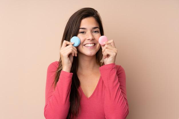Mulher adolescente sobre parede isolada segurando macarons franceses coloridos e sorrindo