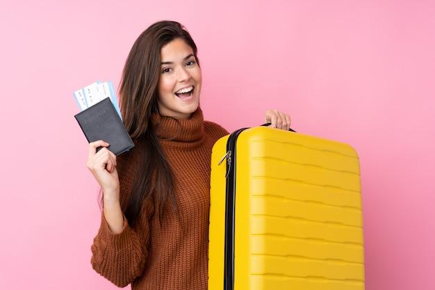 Mulher adolescente sobre parede rosa isolada em férias com mala e passaporte