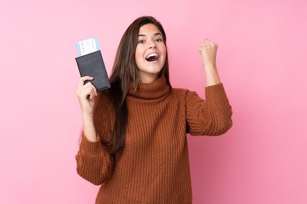 Mulher adolescente sobre parede rosa isolada feliz em férias com bilhetes de avião e passaporte