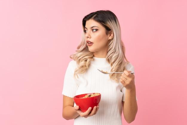 Mulher adolescente sobre rosa isolada, segurando uma tigela de cereais e pensando