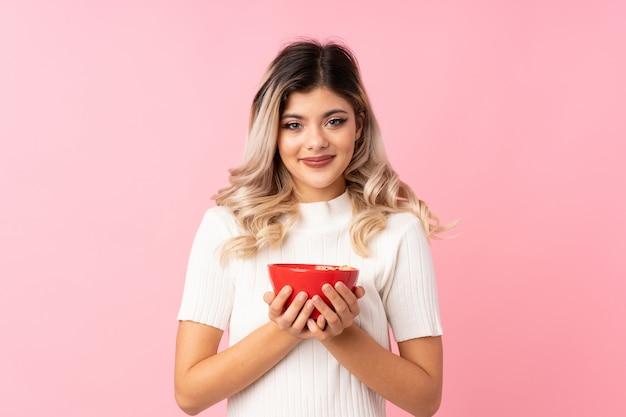 Mulher adolescente sobre rosa isolada, segurando uma tigela de cereais