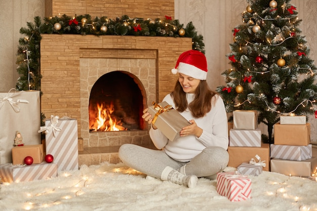Mulher adorável abrindo presente no natal