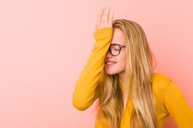 Mulher adorável adolescente esquecendo algo, batendo na testa com a palma da mão e fechando os olhos.