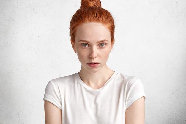 Mulher adorável adorável jovem gengibre confiante com aparência atraente, tem pele pura, vestida com uma camiseta casual, posa contra a parede de concreto branca.
