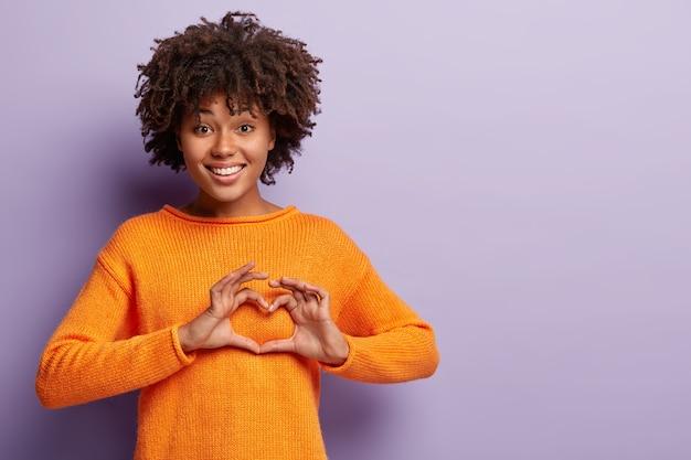 Mulher adorável afetuosa com o coração cheio de amor, mostra a placa do dia dos namorados, vestida com um macacão laranja casual
