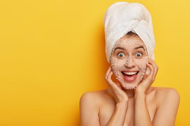 Mulher adorável alegre com expressão facial alegre, aplica máscara natural de sal marinho, tem pele saudável e bem cuidada, usa toalha na cabeça, gosta de tratamentos higiênicos