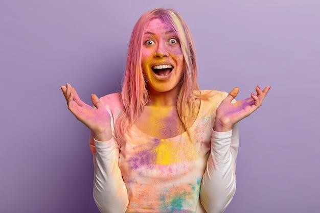 Mulher adorável animada ri alegremente, levanta a mão, tem rosto multicolorido coberto com tinta em pó durante o festival holi, celebra o feriado indiano e a chegada da primavera, modelos sobre parede roxa