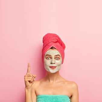 Mulher adorável aponta o dedo indicador para cima, usa máscara nutritiva, reduz as espinhas, evita problemas de ressecamento da pele, enrolada em toalha de banho