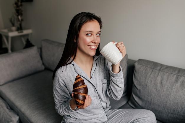 Mulher adorável atraente com sorriso maravilhoso de pijama, bebendo café e comendo croissants em casa em um bom dia de sol.