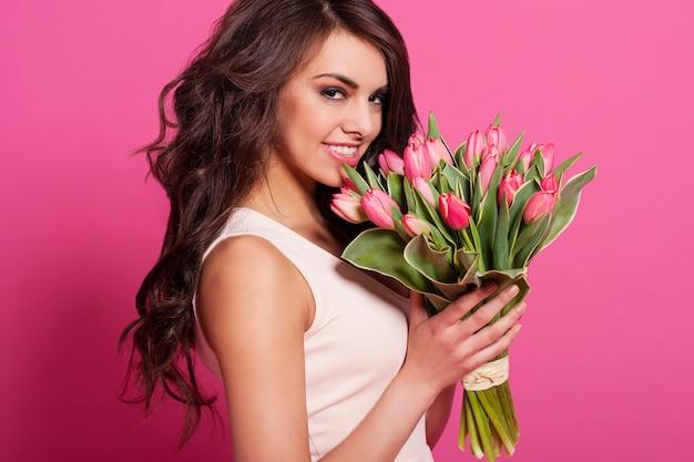 Mulher adorável com buquê de tulipas cor de rosa
