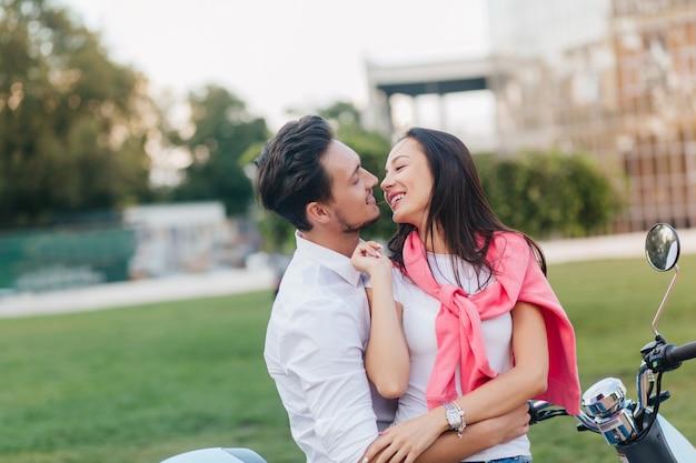 Mulher adorável com cabelo preto beijando o marido de forma divertida num bom dia de verão no fundo da natureza