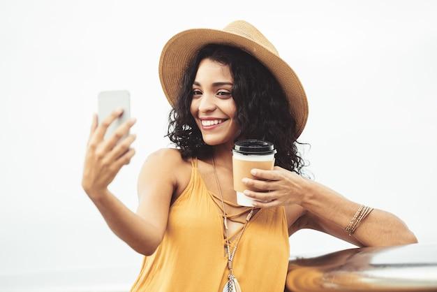 Mulher adorável com café para viagem, tendo selfie ao ar livre