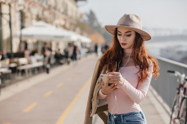 Mulher adorável com camisa rosa verificando o correio do celular