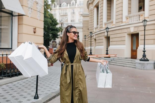 Mulher adorável com casaco de outono passando um tempo na cidade, indo para a loja